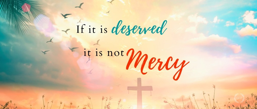 "image of quote ""if it is deserved, it is not mercy"" with sunset and cross"