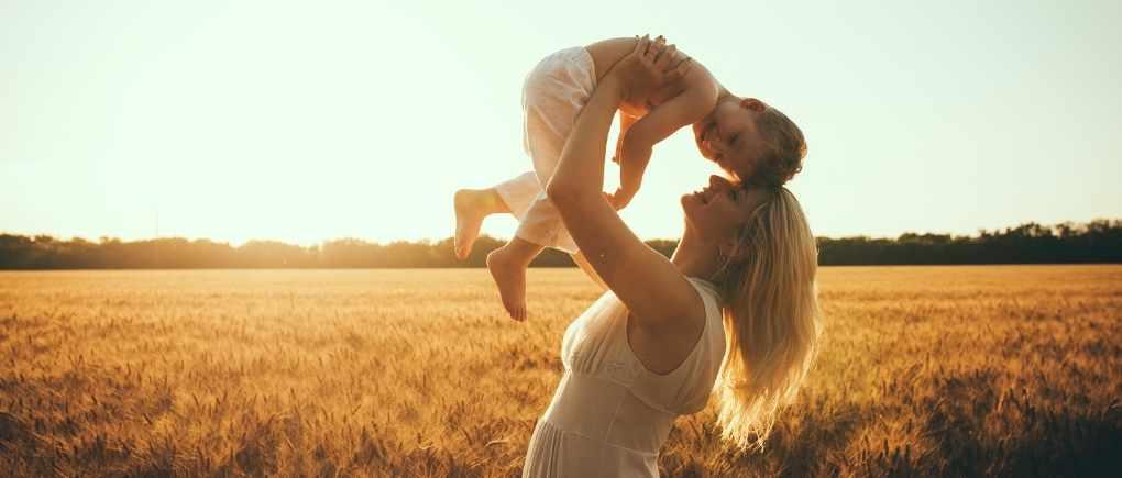 woman holding her preschool son in a field