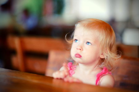 image of a small girl looking up with her mouth closed because she's been told children should be seen and not heard